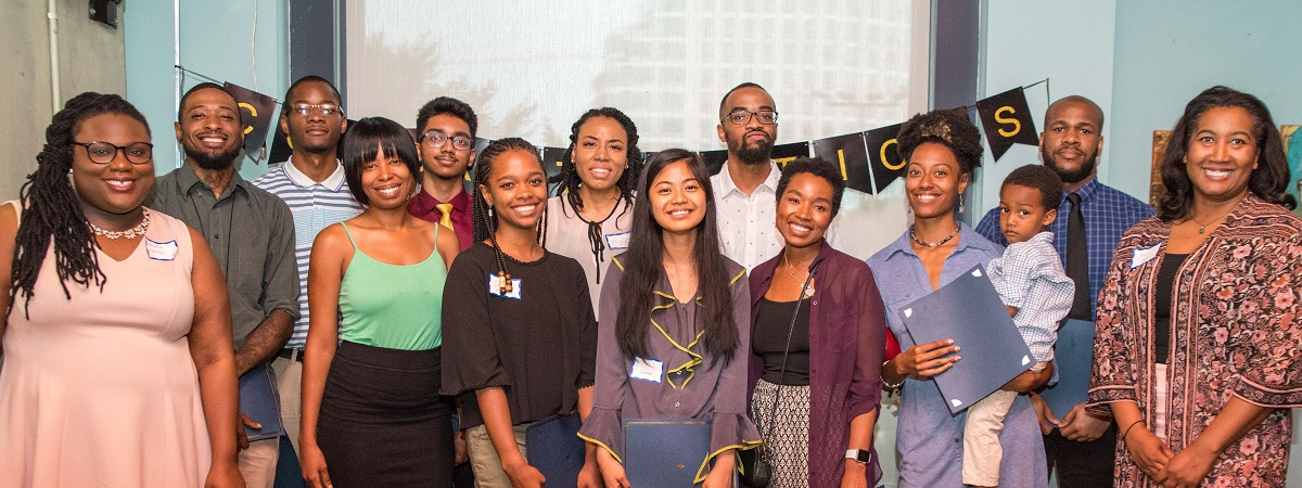 A large group of smiling African Americans gather at a Alpha Cohort Completion Event