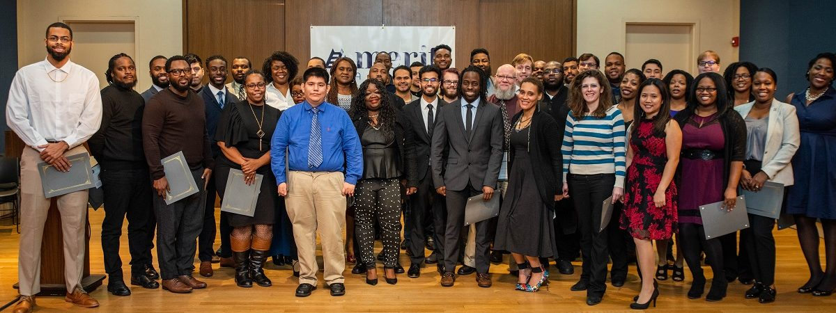 A huge group of recent graduates gather and smile at their Beta Cohort Graduation