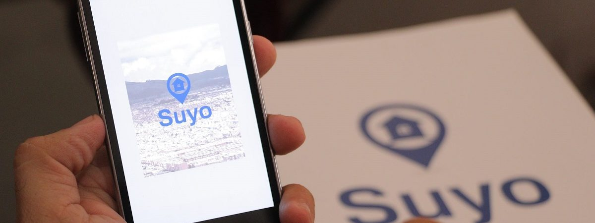 A hand holds out a cell phone with the Suyo app open on the screen