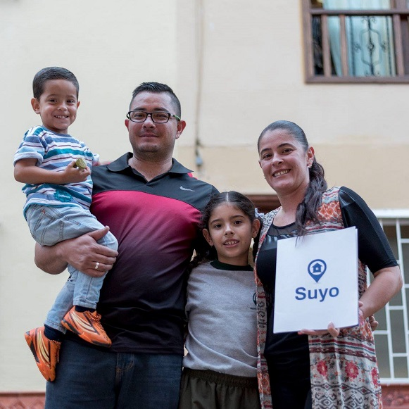 A smiling family of four stands in front of their home in Latin America