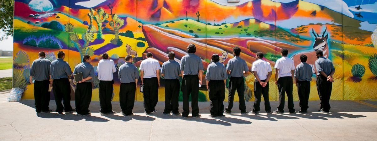 A group of AIYN youth stand facing a colorful mural on a wall
