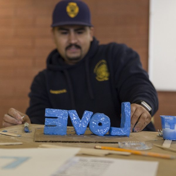 AIYN probation officer paints letters that spell out love in the color blue