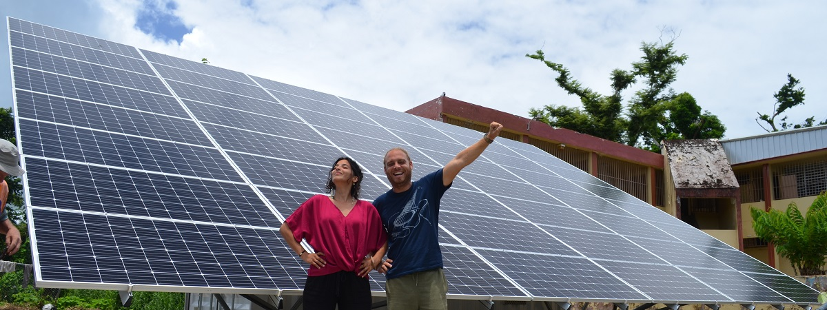 A woman and a man stand in front of solar panels