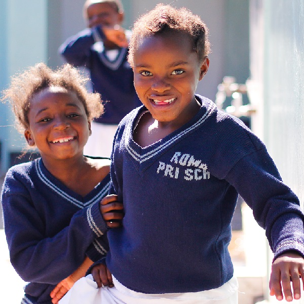 3 African school children smile on the playground
