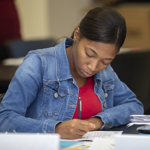 A young black female teacher works at a desk in a school