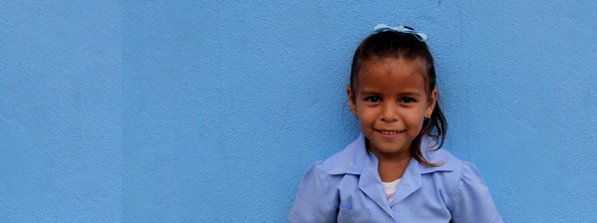 Small Costa Rican schoolgirl stands in a blue dress in front of a blue wall